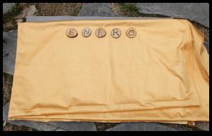 Fielto con tela de color dorada. Sobre ella hay 5 rodajas de madera que forman la palabra Enero en mayúscula